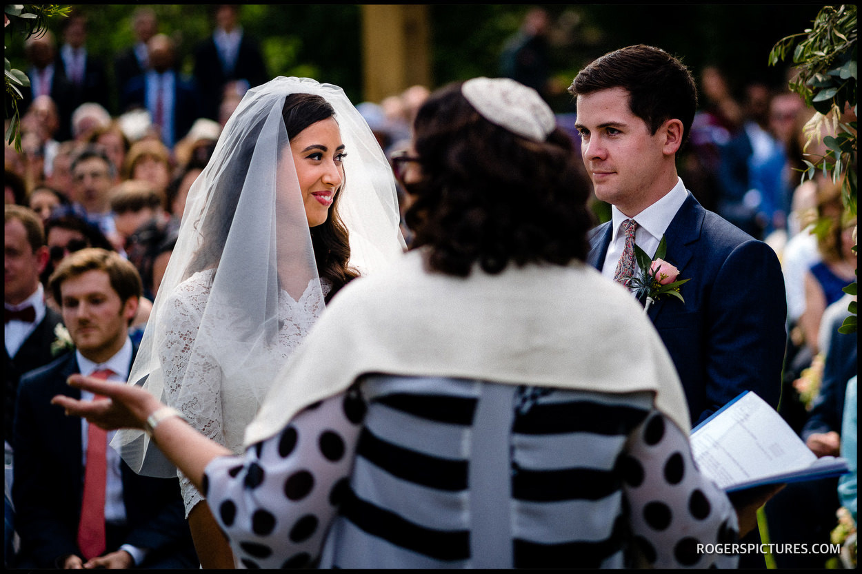 Bride and groom say their vows under the Chuppah in the garden