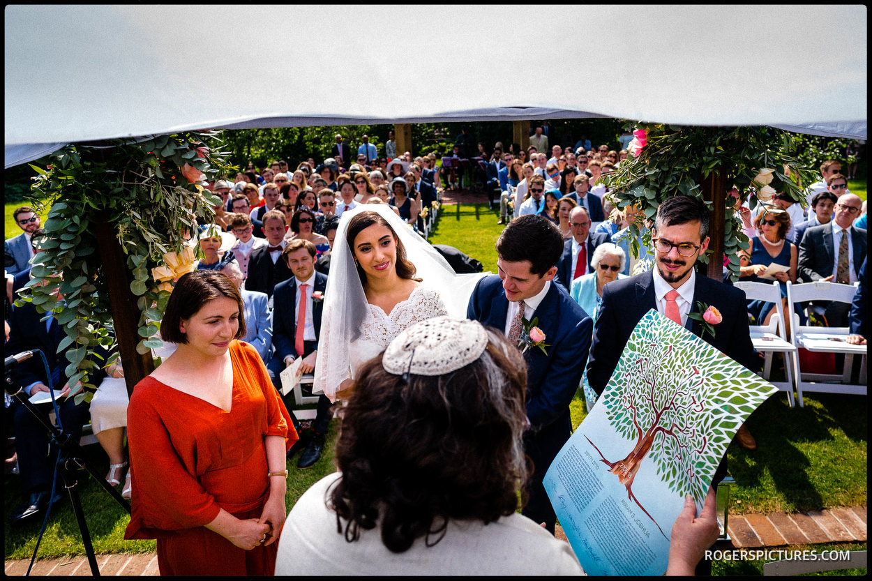 Rabbi with the Ketubah under the Cguppah at Jewish Oxfordshire wedding