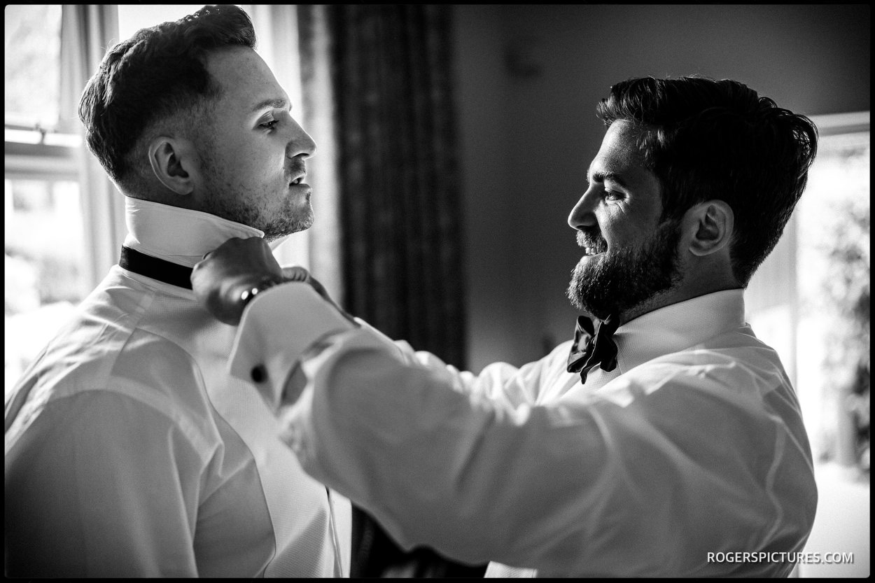 Photojournalism of groom and best man getting ready