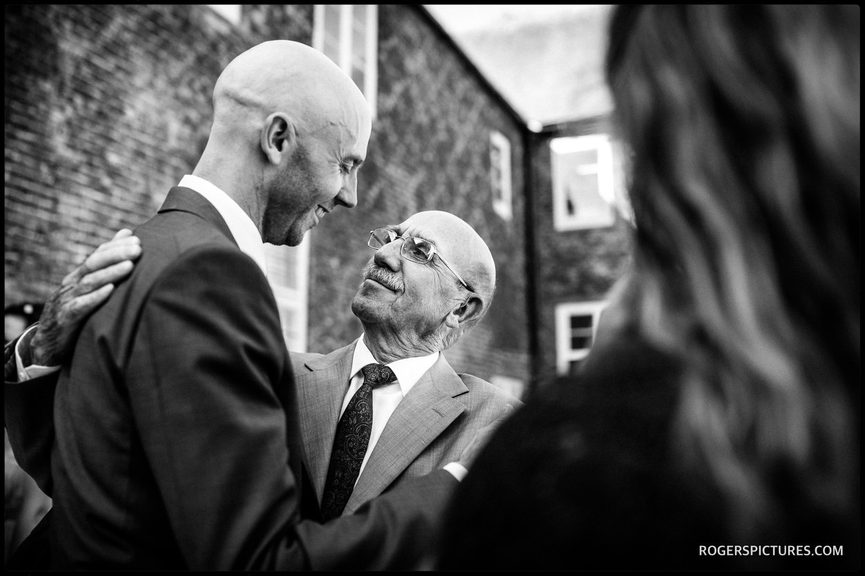 Groom and father hug at Fulham Palace wedding in London