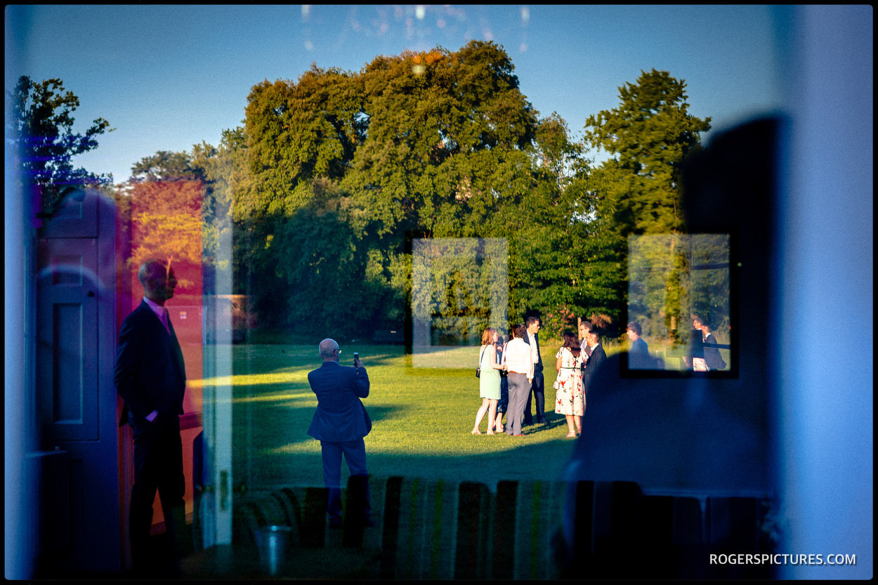 Guests in the gardens at Fulham Palace summer wedding