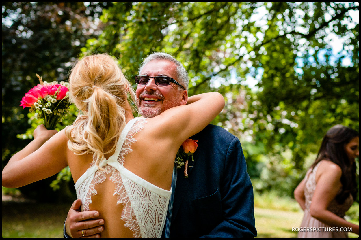 Father hugs his daughter before her North London garden wedding ceremony