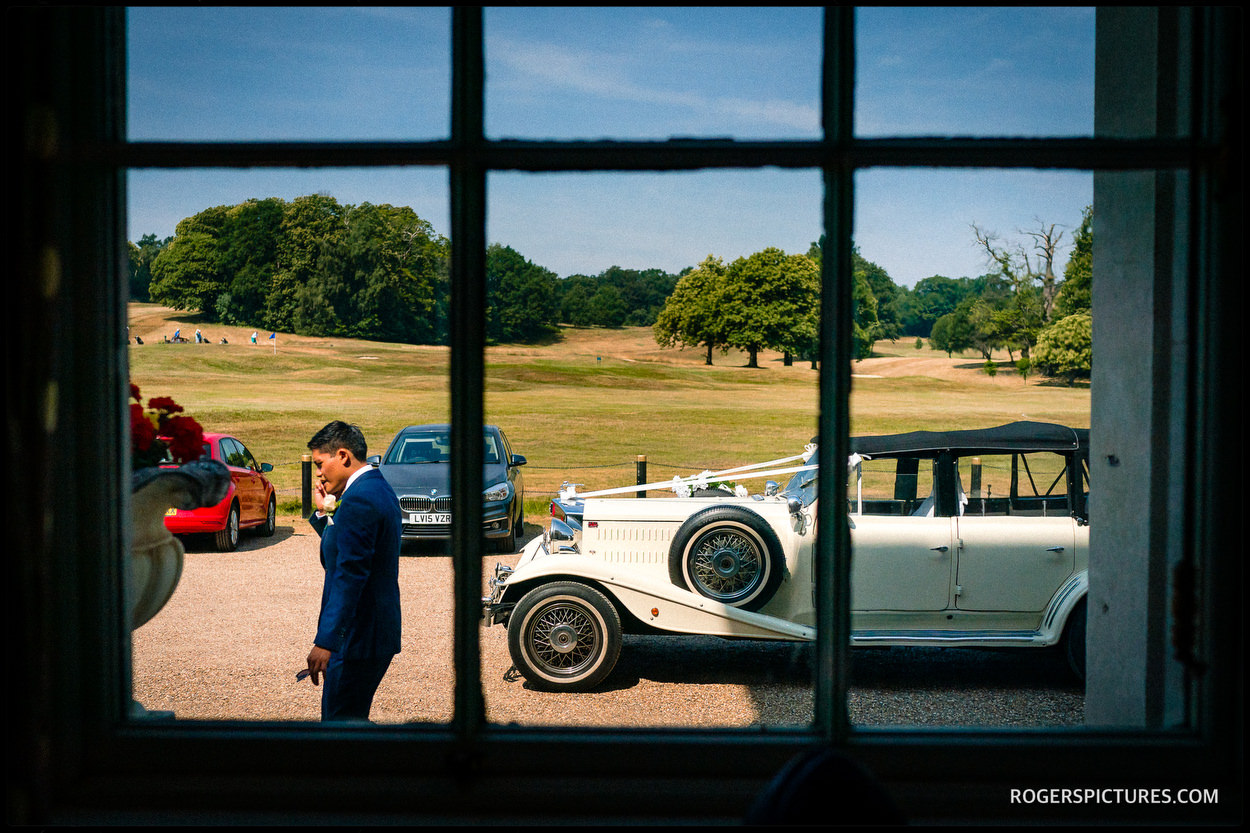 Groom and wedding car in the Summer sun