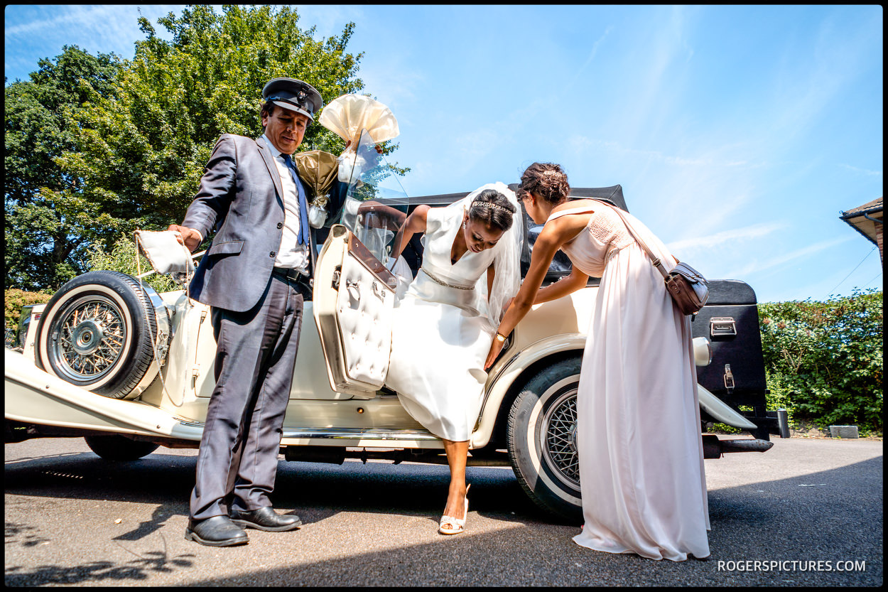 Bride arrives in vintage wedding car
