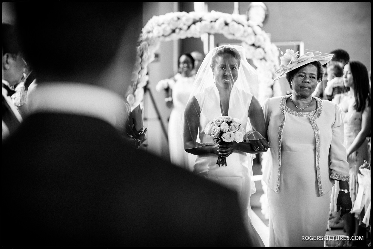 Black and white picture of bride and Mum walking down the aisle