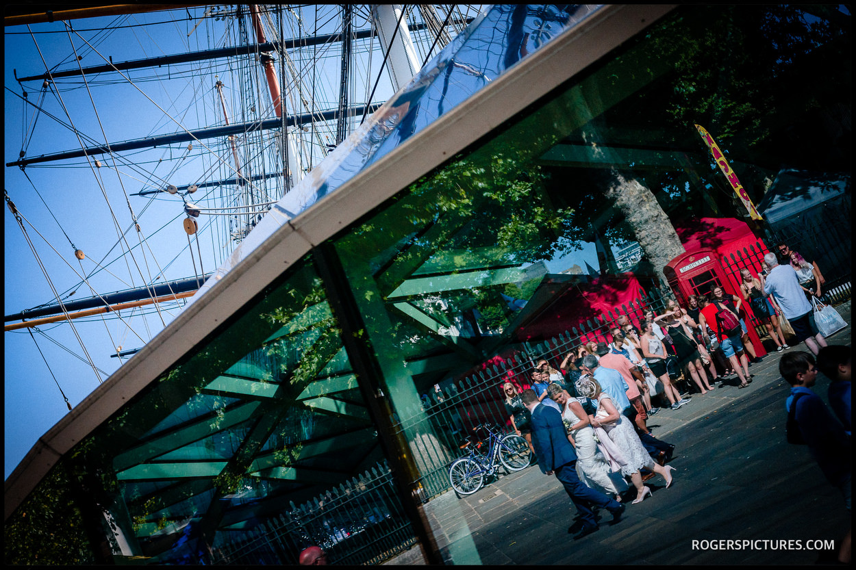 Bride and groom walk past the Cutty Sark in Greenwich