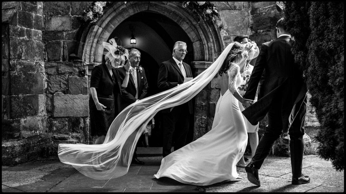 Black and white documentary wedding photo of a bride and veil outside church