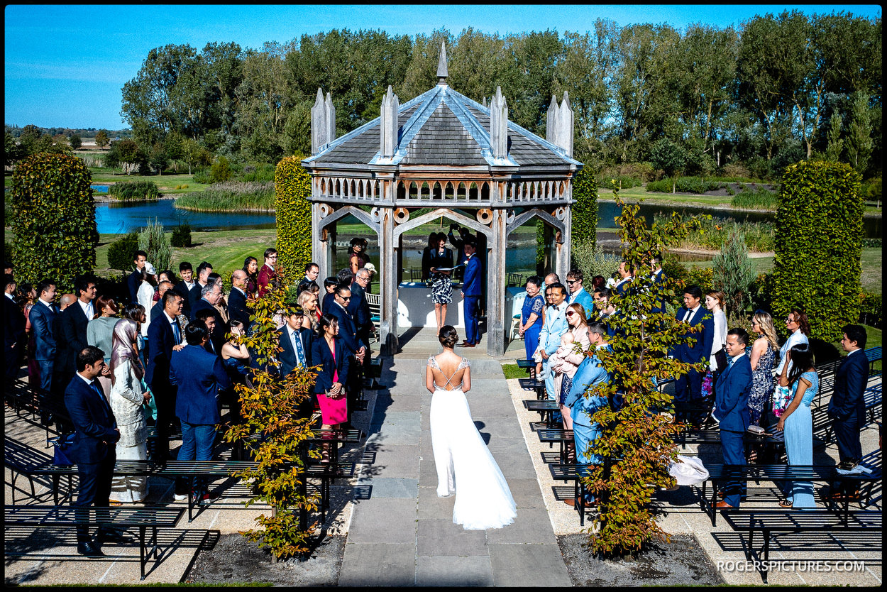 Bride walks down the aisle at the Garden Pavilion at Old Hall Ely