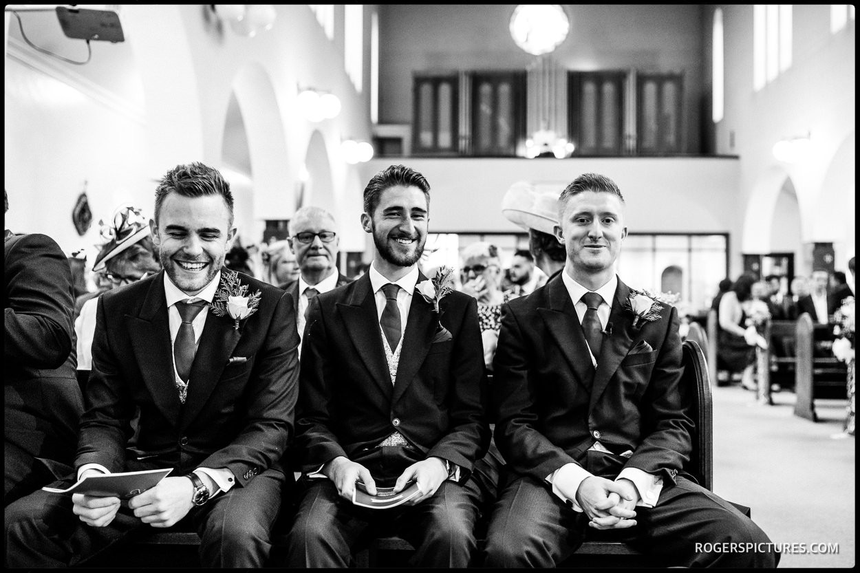 Groom and groomsmen wait in church for bride's arrival