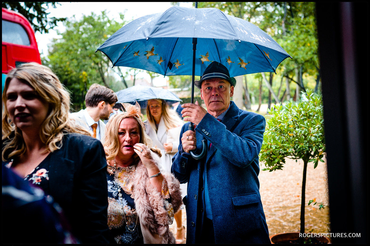 Guests with umbrellas at a wedding at Stoke Place Hotel in Buckinghamshire