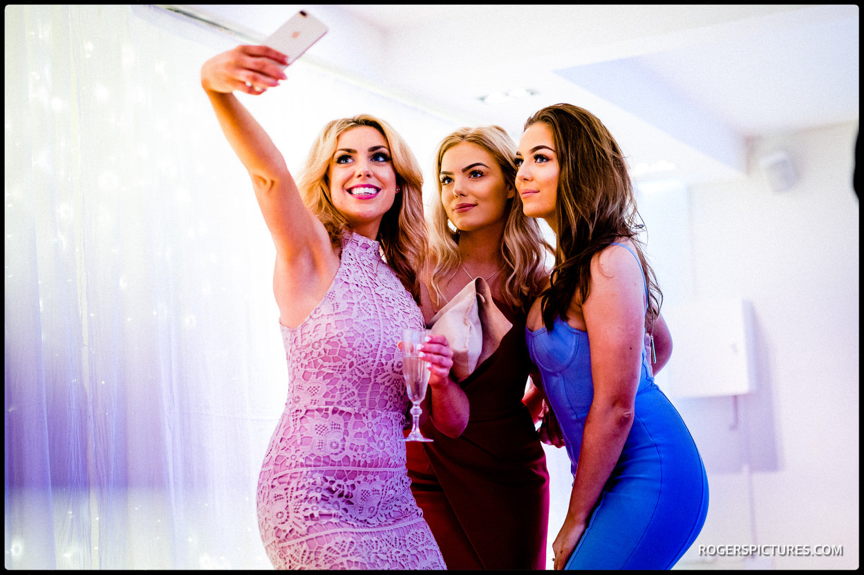 Guests take a selfie at a wedding at Stoke Place Hotel in Buckinghamshire