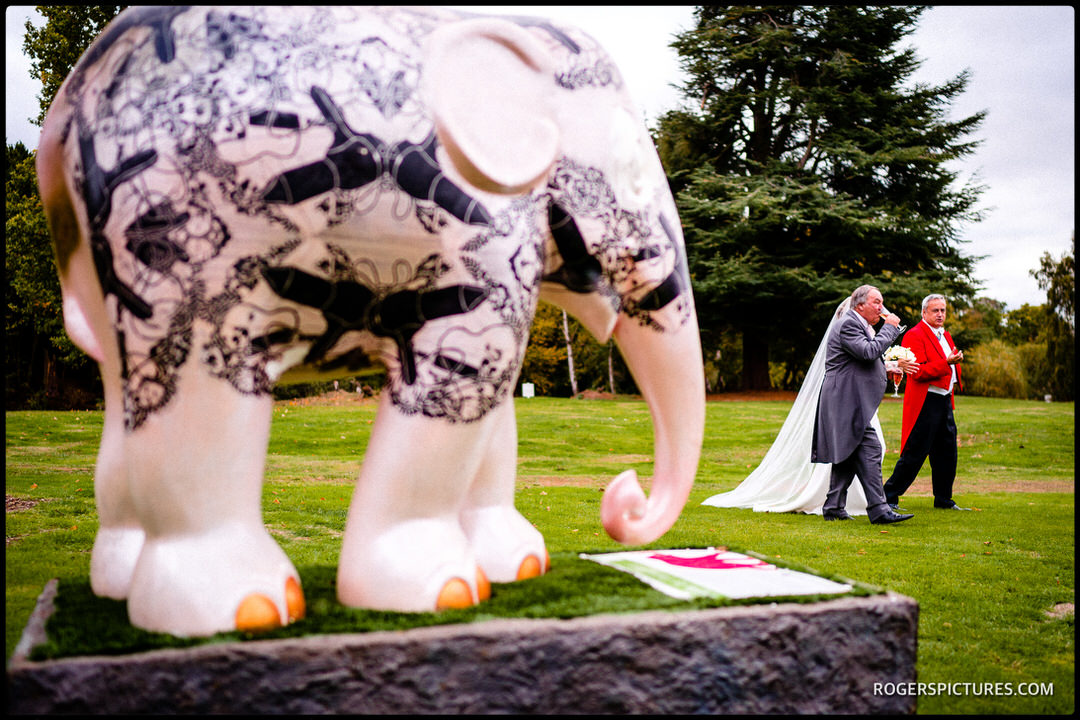 Bride and groom walk past the elephant at Stoke Place Hotel