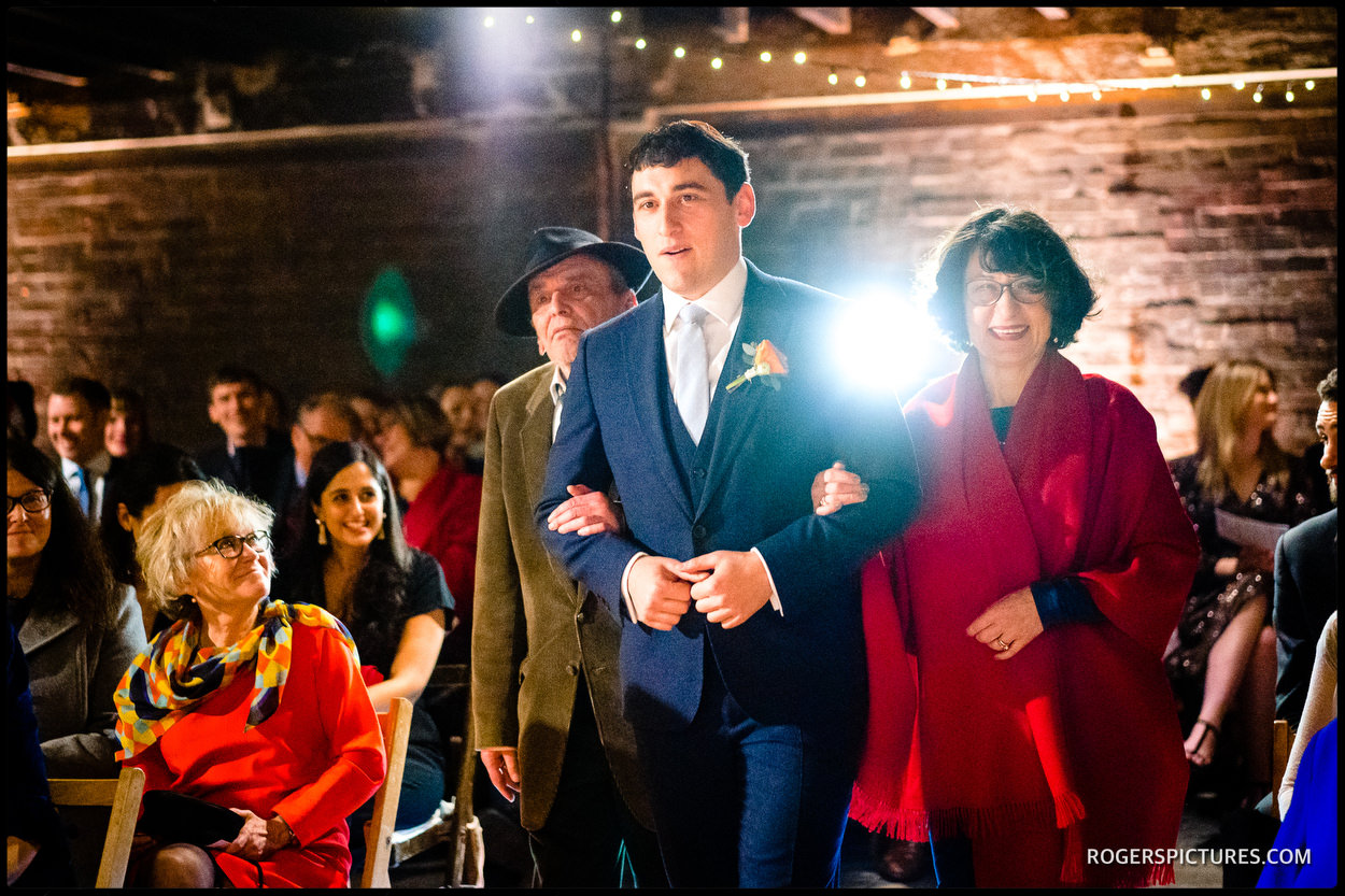 Groom and parents at Jewish wedding at Electrician's workshop