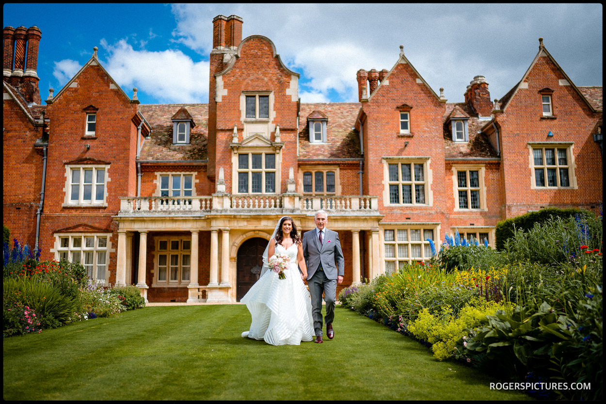 Father walks his daughter to an outdoor wedding ceremony at Longstowe Hall