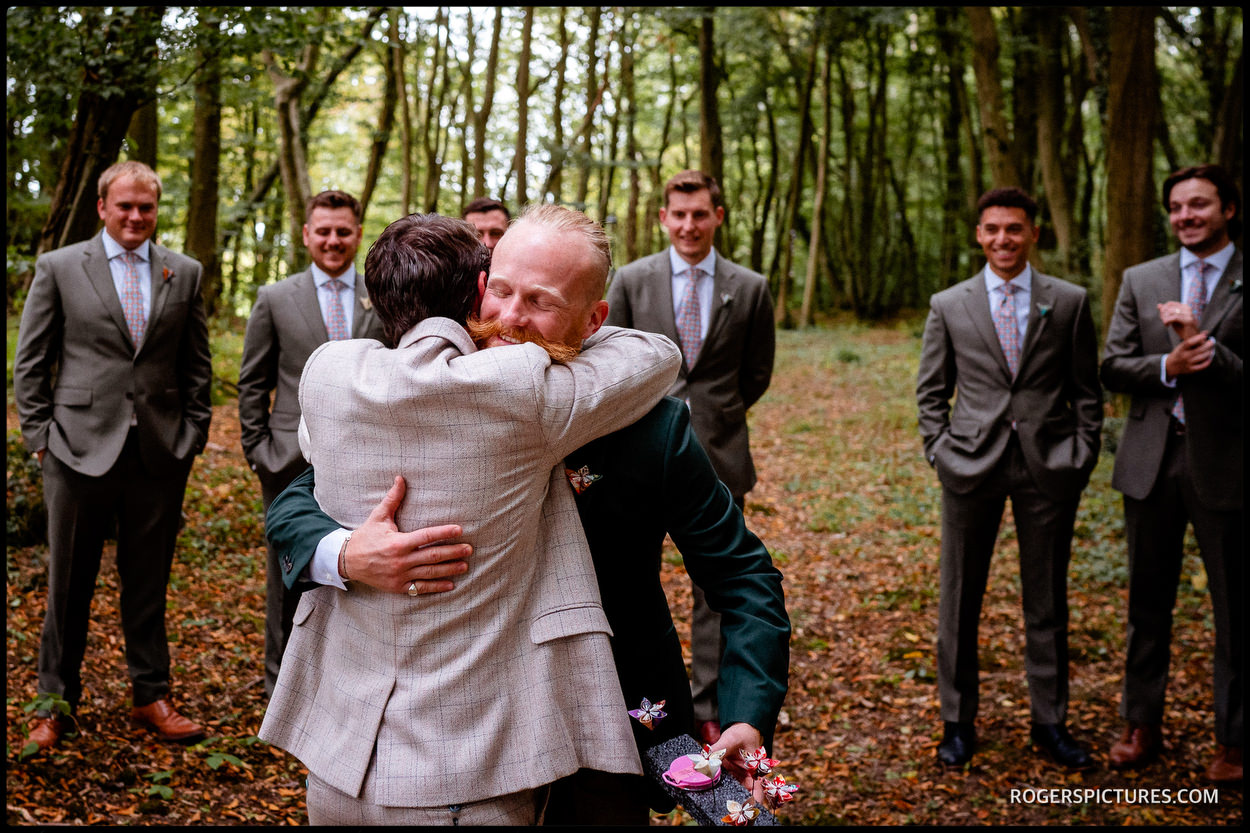 Groom greeting groomsmen in the forest