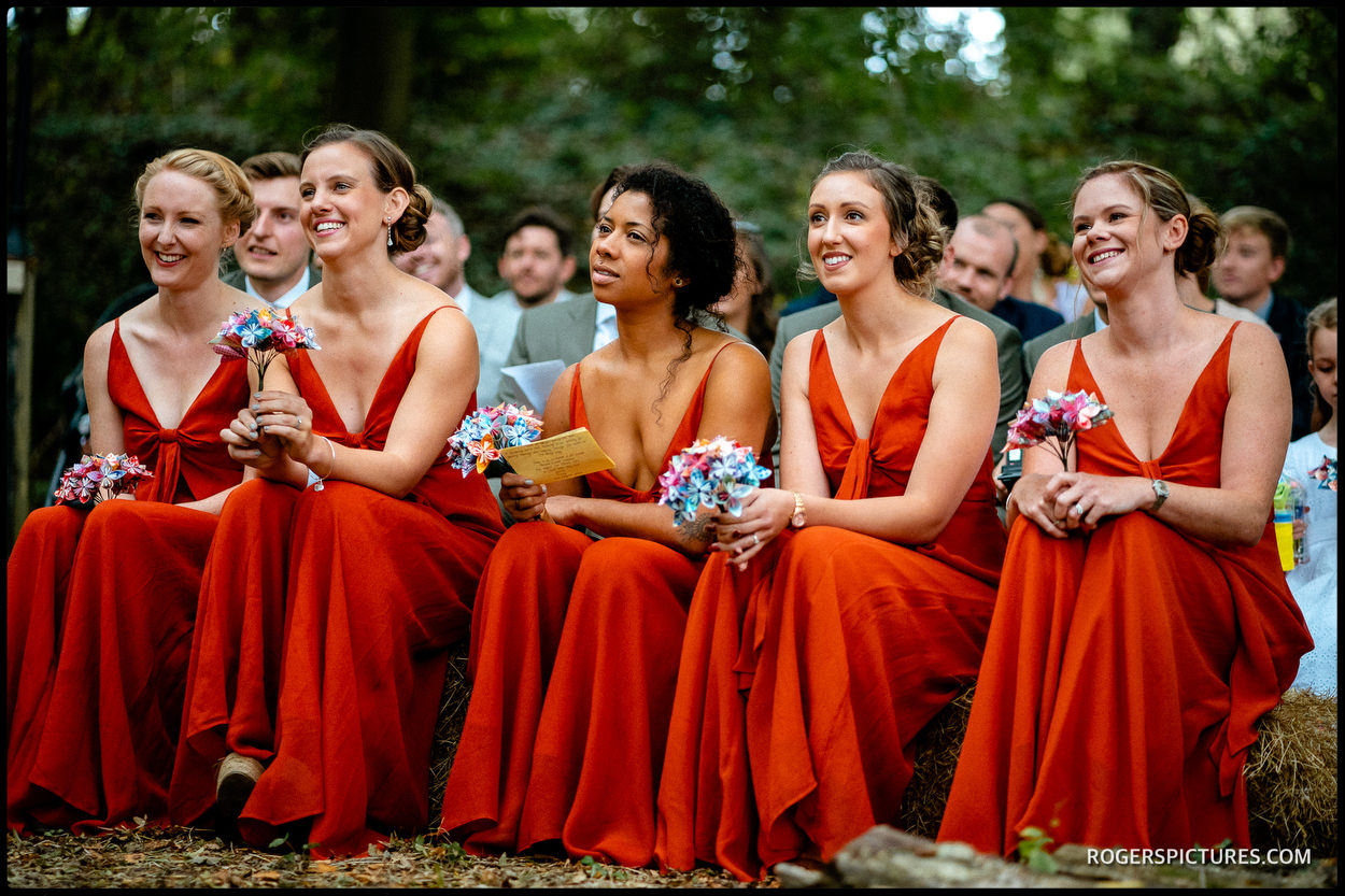 Bridesmaids in red dresses on a hay bale at Swallows Oast wedding