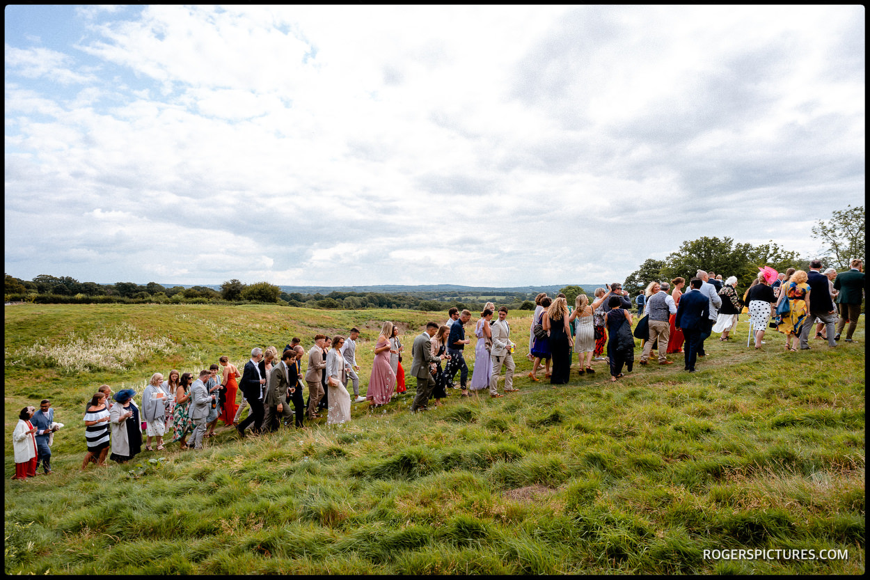 Wedding guests walk up a hill at outdoor wedding