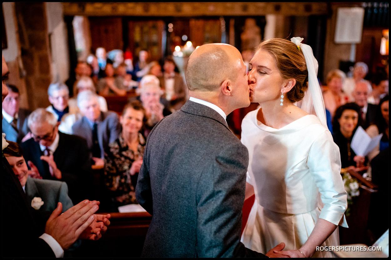 Devon church wedding bride kisses groom
