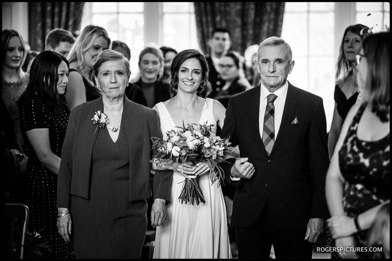 Bride with parents walks down the aisle
