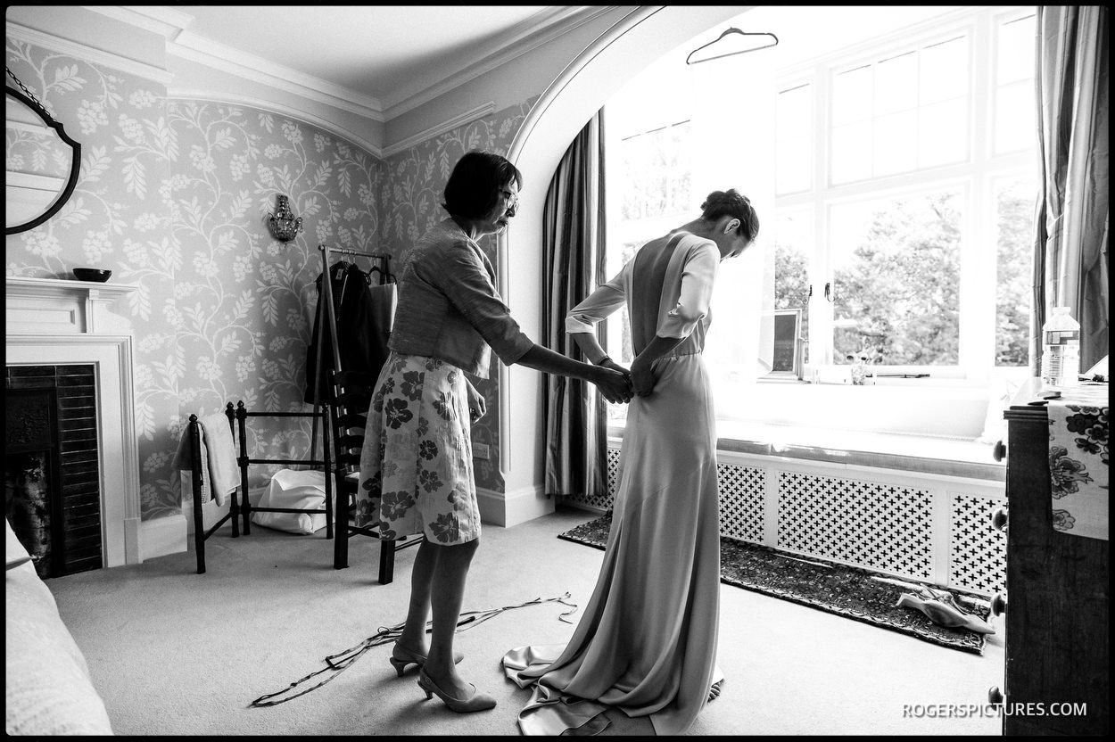 Black and white photo of bride getting dressed for her wedding in Cambridge