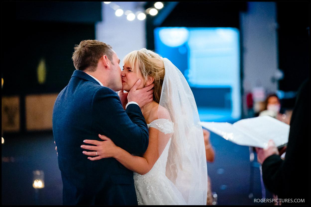 Husband and wife kiss at church wedding in Watford