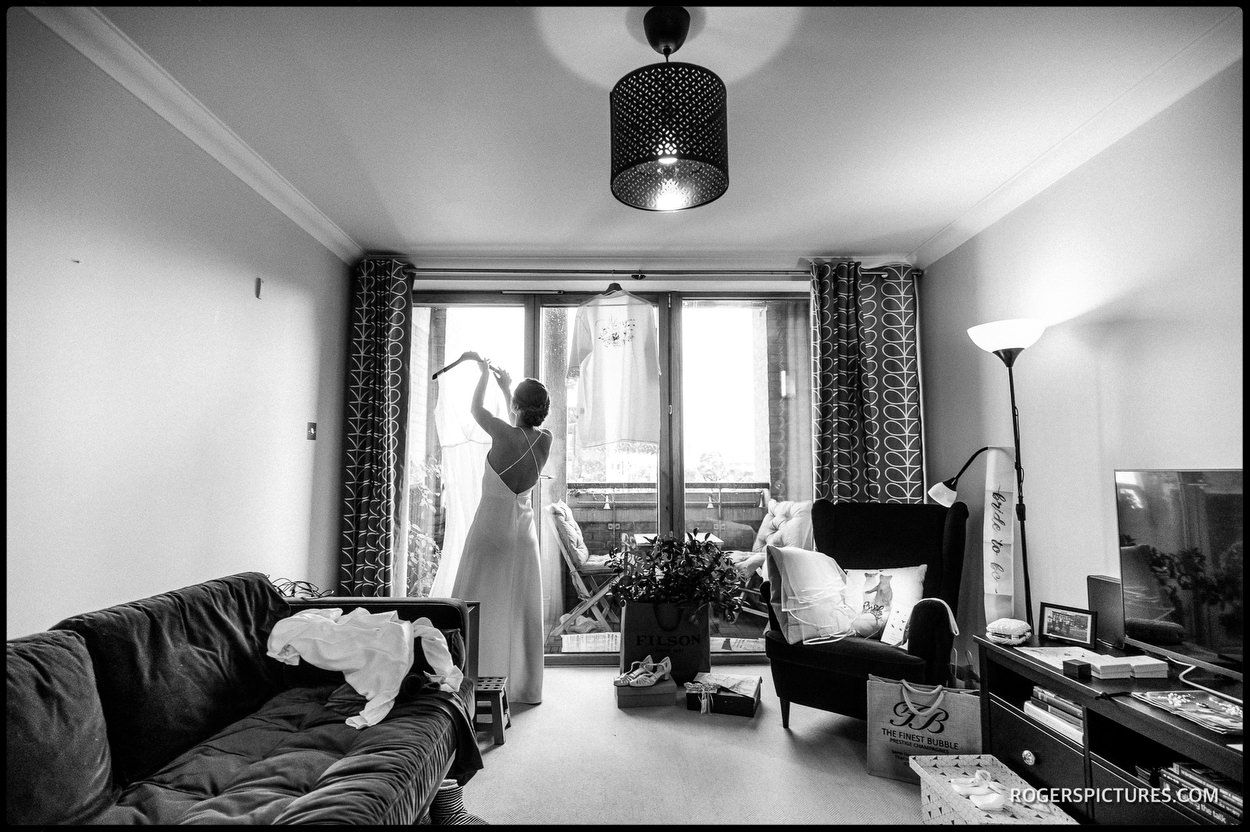 Black and white photo of bride getting dressed