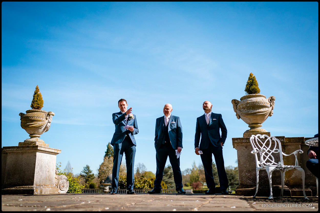 Groom and best men deliver wedding speeches outside at Luton Hoo