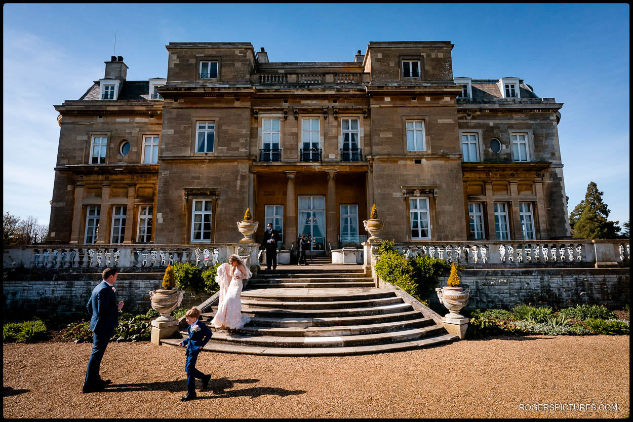 Bride in wedding dress on the steps outside Luton Hoo in Bedfirdshire