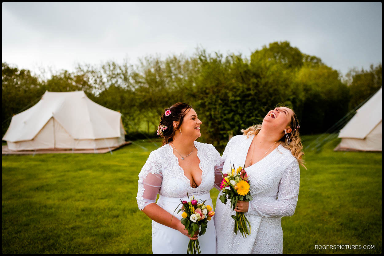 Two brides at glamping wedding with tents in the background