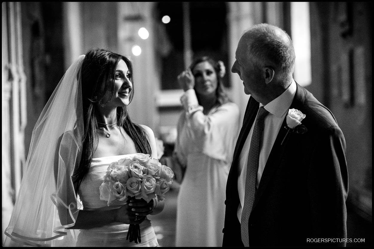 Black and white photo of bride and father in cathedral