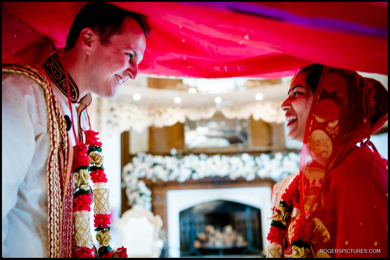Subho Dristi as the bride and groom exchange looks at Froyle Park wedding