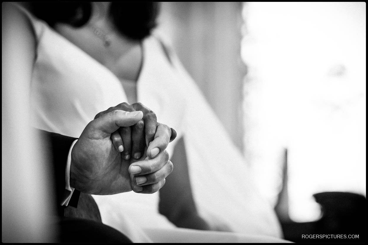 Detail of newly married couple holding hands