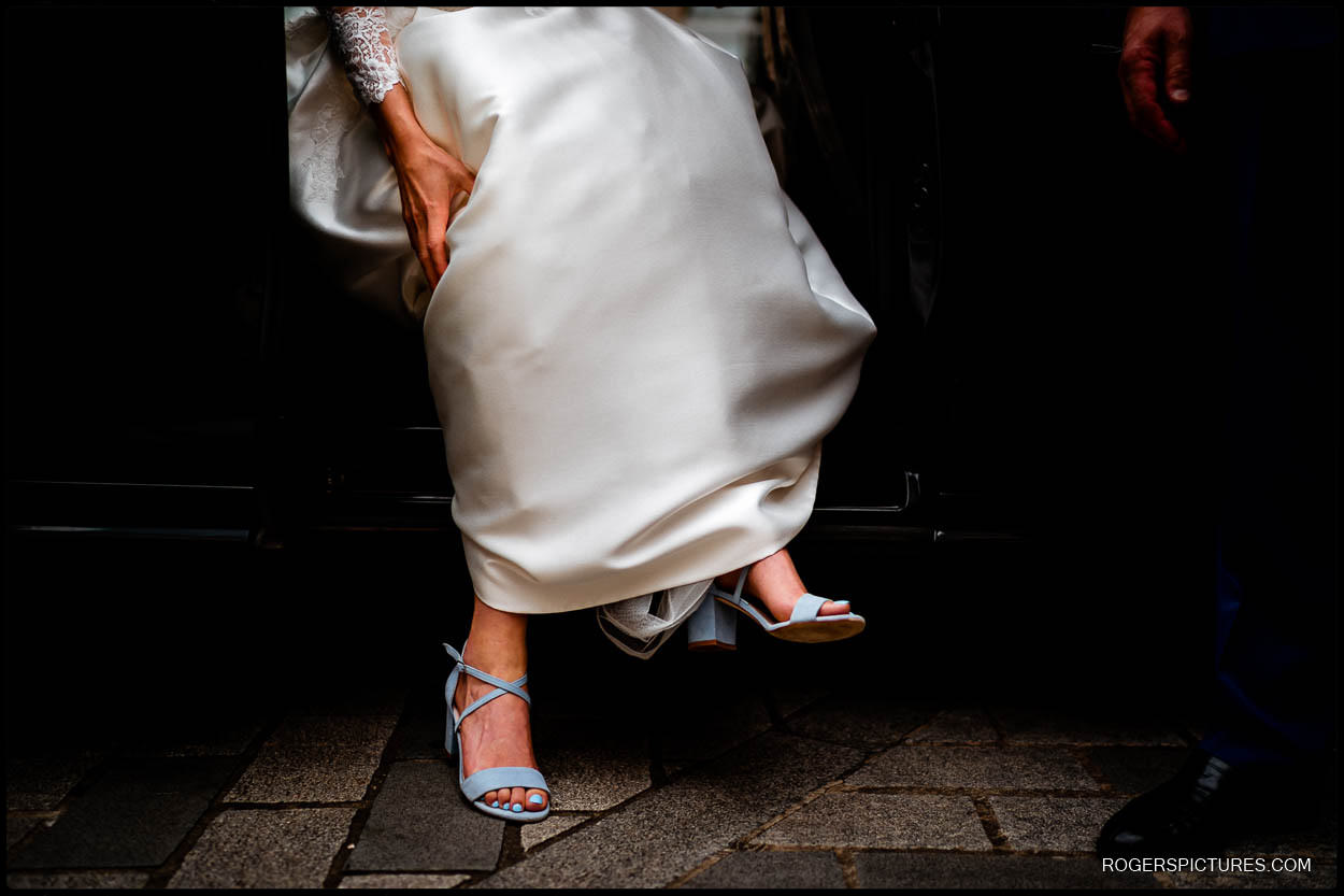 Bride steps out of London taxi in pale blue Harriet Wilde wedding shoes