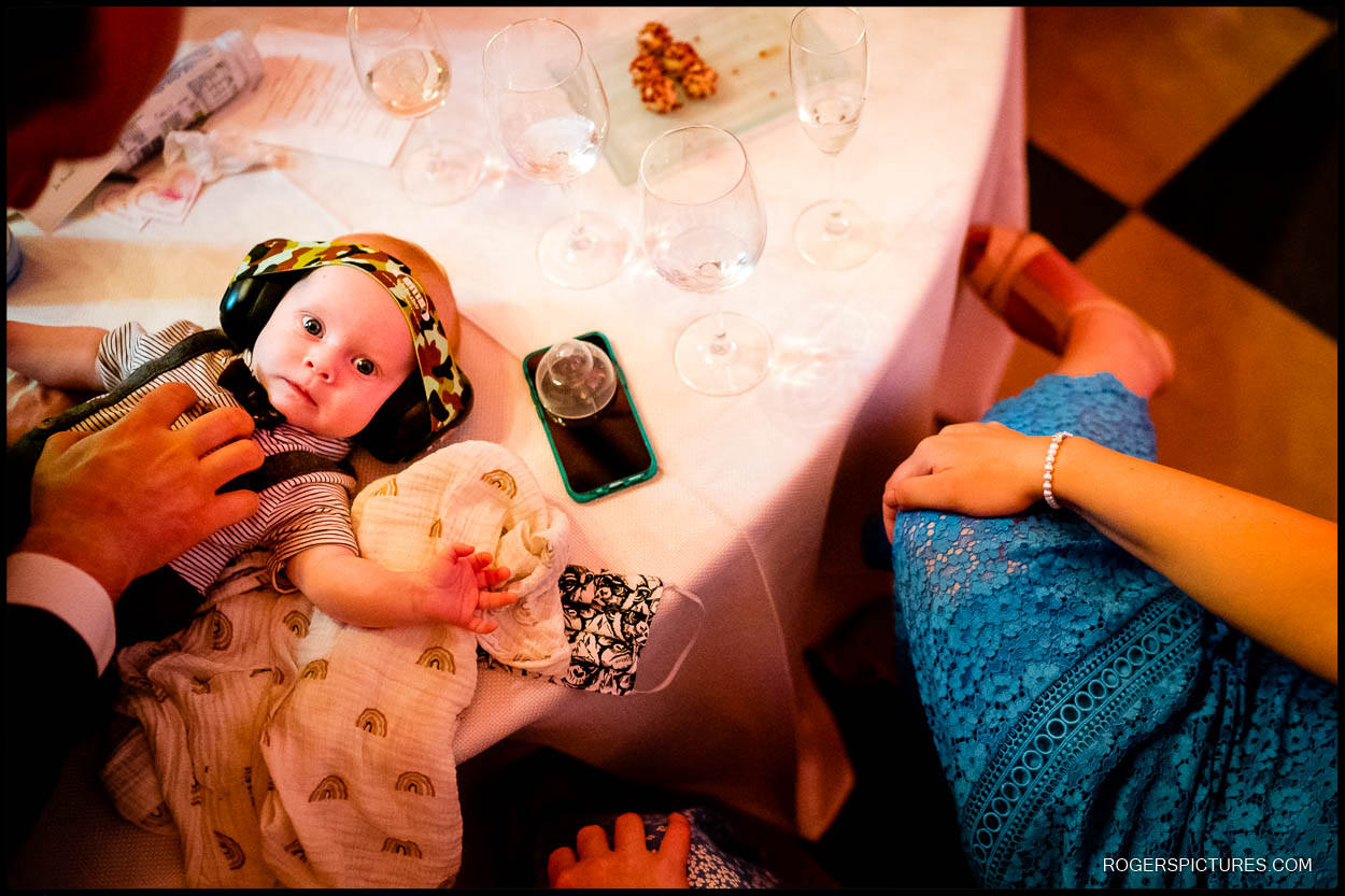 Baby with ear protectors at a wedding reception in London